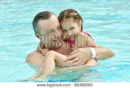 Dad and daughter relax in  pool