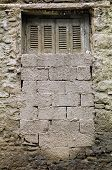 image of oddities  - Bricked up window and textured wall of a derelict house - JPG