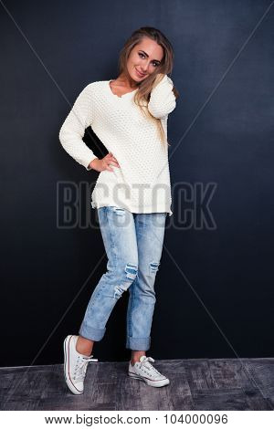 Full length portrait of a happy cute woman standing on gray background