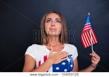 Portrait of a happy patriotic woman holding USA flag and looking up over gray background