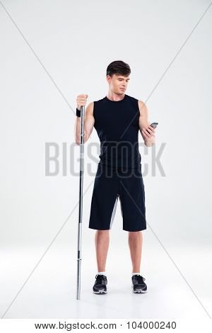 Full length portrait of a handsome man holding barbell and using smartphone isolated on a white background