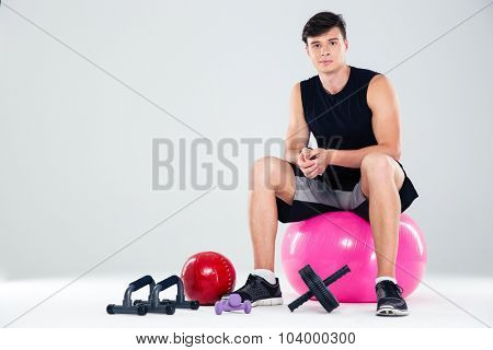 Portrait of a sports man sitting on the fitness ball isolated on a white background
