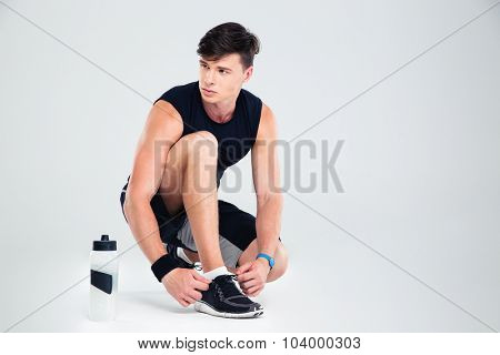 Athletic man tie shoelaces while looking away isolated on a white background