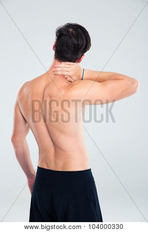 Back view portrait of a man having neck pain isolated on a white background
