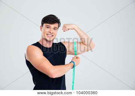 Portrait of a happy fitness man measuring his biceps isolated on a white background