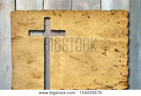 Concept or conceptual Christian cross cut in an old grungy or vintage paper, over a wood texture background