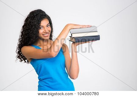 Portrait of a happy afro american woman holding books isolated on a white background