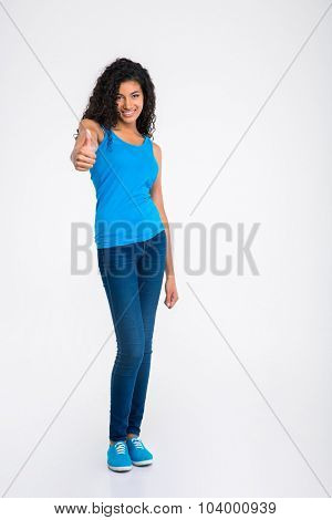 Full length portrait of a cheerful afro american woman showing thumb up isolated on a white background