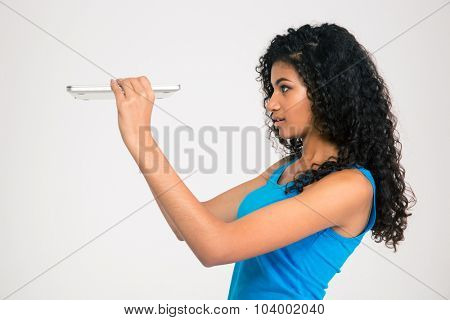 Portrait of a happy afro american woman looking on thin laptop computer isolated on a white backgorund