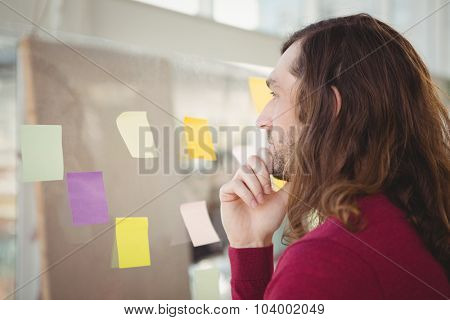 Thoughtful man looking at adhesive notes stuck on glass in office