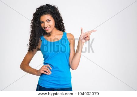 Portrait of a smiling afro american woman pointing finger away isolated on a white background
