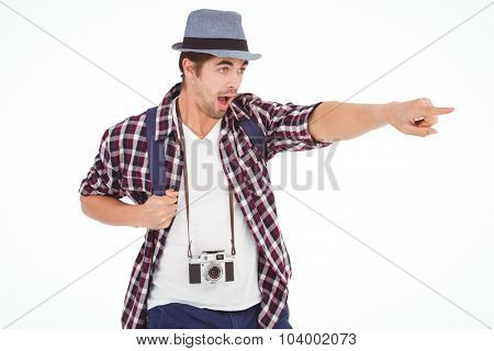 Surprised man with backpack pointing against white background