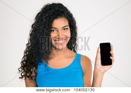 Portrait of a smiling afro american woman showing blank smartphone screen isolated on a white background