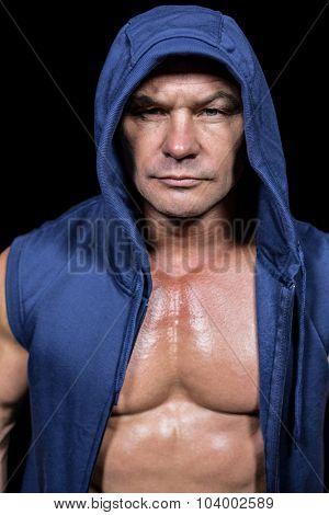 Portrait of muscular man in blue hood against black background