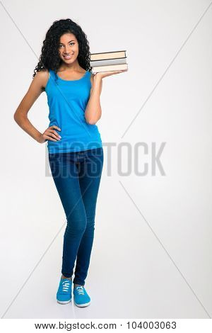 Full length portrait of a happy afro american woman holding books isolated on a white background