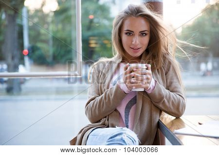 Portrait of a happy girl drinking coffee in cafe and looking at camera
