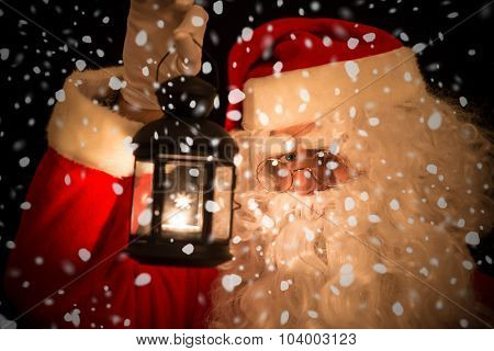 Santa Claus holding a lantern to see in the dark