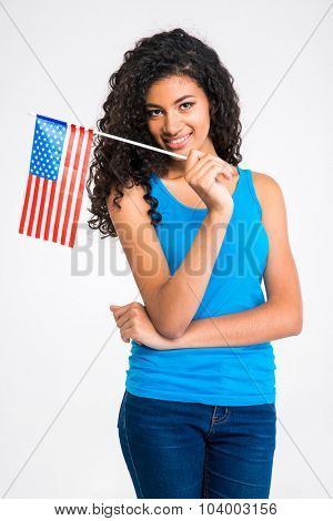 Portrait of a happy casual afro american woman holding USA flag isolated on a white background and looking at camera