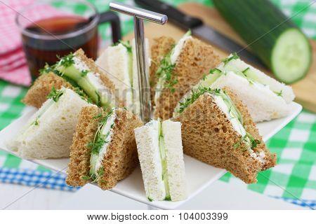 White and brown cream cheese and cucumber sandwiches on cake stand