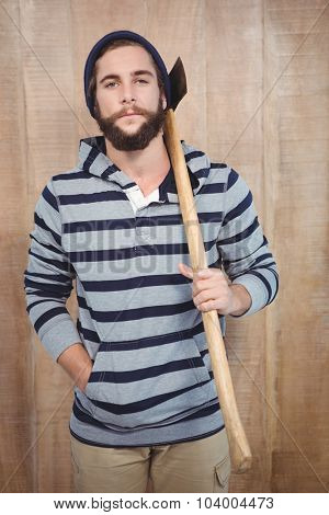 Portrait of hipster with hooded shirt holding axe against wooden wall