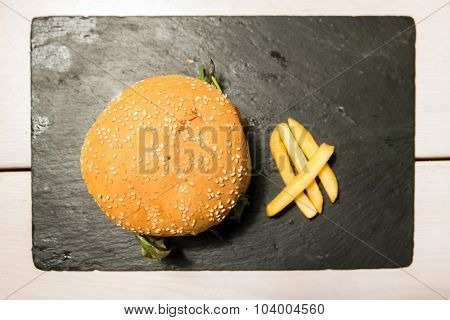 Tasty hamburger served on a black stone with french fries