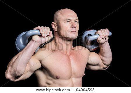 Muscular fit man holding dumbbells against black background