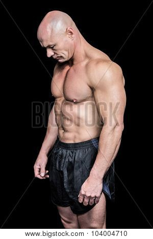 Side view of sad bald man looking down against black background