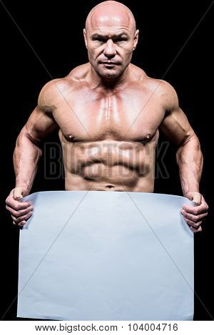Portrait of shirtless man holding blank paper against black background