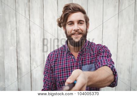 Portrait of hipster using selfie stick against wooden wall