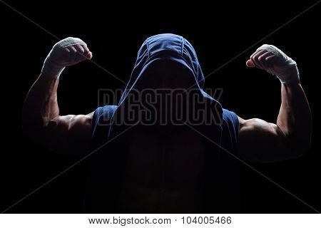 Athlete in hood flexing muscles against black background