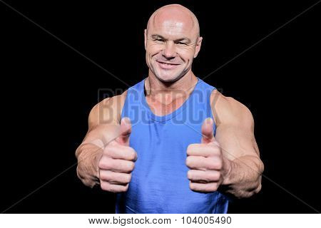 Smiling healthy man showing thumbs up against black background