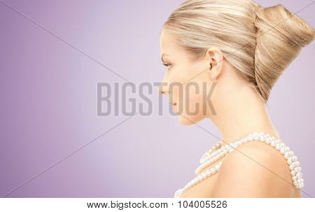 beauty, luxury, people, advertisement and jewelry concept - beautiful woman with sea pearl necklace or beads over violet background