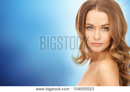 people, beauty, hair and skin care concept - beautiful woman with curly hairstyle over blue background