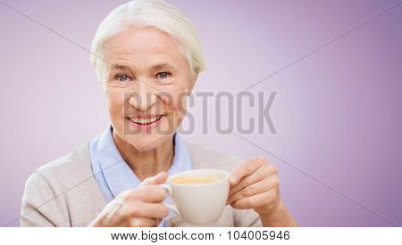 age, drink and people concept - happy smiling senior woman with cup of coffee over violet background