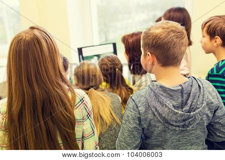 education, elementary school, learning, technology and people concept - group of school kids with teacher looking to computer monitor in classroom from back