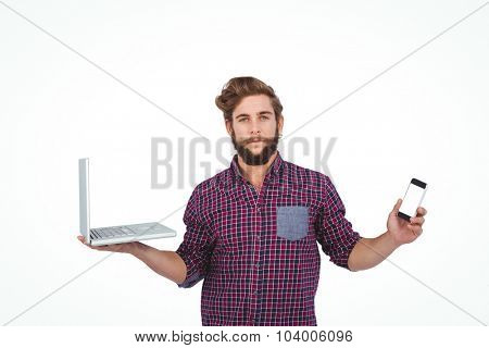 Portrait of serious hipster with smartphone and laptop standing against white background
