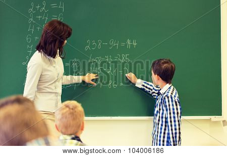 education, elementary school, learning, math and people concept - close up of little schoolboy with teacher writing on chalk board and solving task in classroom