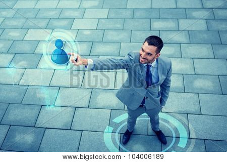 business, development, technology, connection and people concept - young smiling businessman pointing finger to user icon on virtual screen outdoors from top