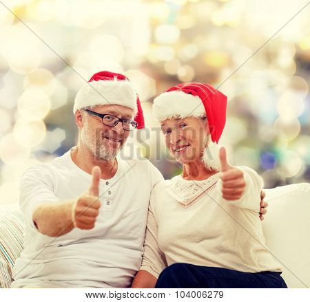 family, holidays, christmas, age and people concept - happy senior couple in santa helper hats sitting on sofa over lights background and showing thumbs up gesture