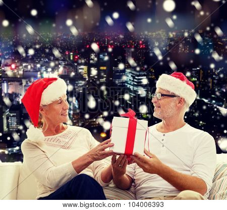family, holidays, christmas, age and people concept - happy senior couple in santa helper hats with gift box over snowy night city background