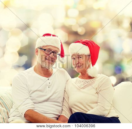 family, holidays, christmas, age and people concept - happy senior couple in santa helper hats sitting on sofa over lights background