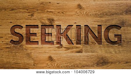 The word Seeking Engraved in Wooden Background