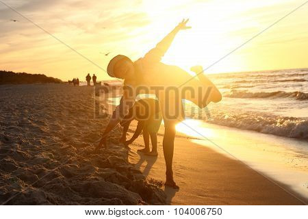 Children boy and girl playing on the sea shore on a sandy beach during sunset