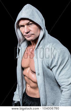 Portrait of muscular man in hood against black background