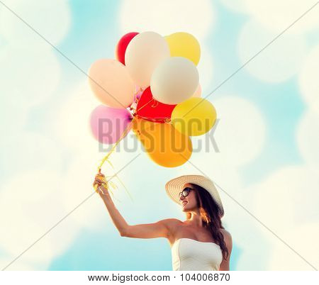 happiness, summer, holidays and people concept - smiling young woman wearing sunglasses with balloons over blue lights background