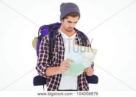 Man with luggage looking in map while standing against white background