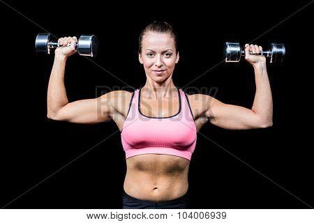 Portrait of smiling woman lifting dumbbells against black bakground