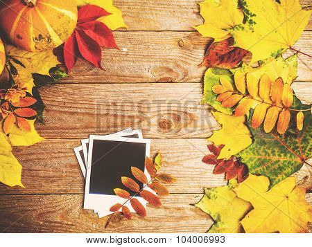 Autumn background with colorful leaves and pumpkins on rustic wooden board. Creating fall season memories with retro photo cards of photo frames. Thanksgiving and Halloween holidays concept. Copyspace