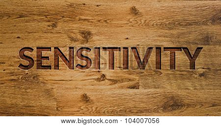 The word Sensitivity Engraved in Wooden Background
