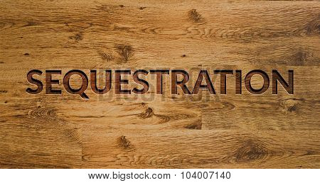 The word Sequestration Engraved in Wooden Background